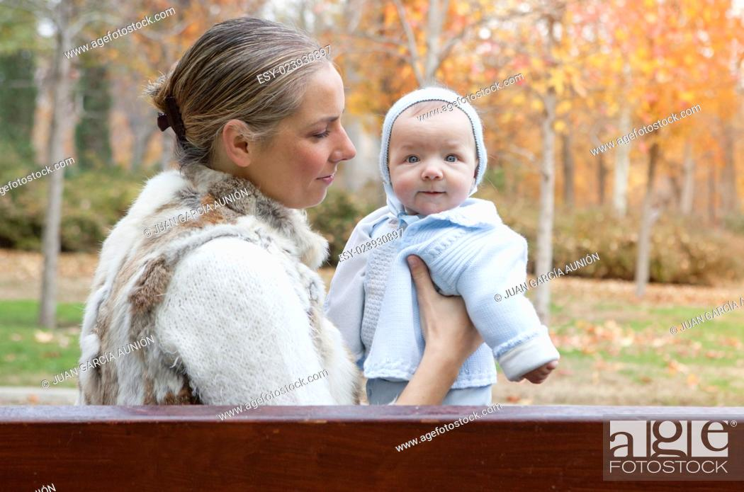 Stock Photo: Happy mother playing with his baby in the park on the bench on winter season.