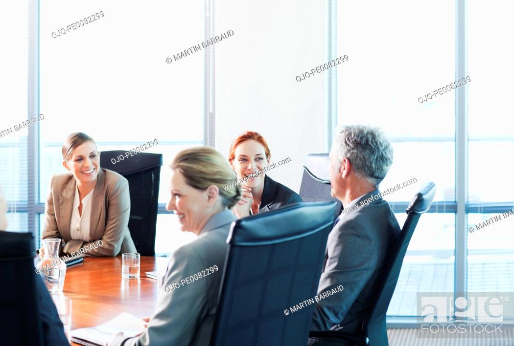 Stock Photo: Smiling business people meeting at table in conference room.