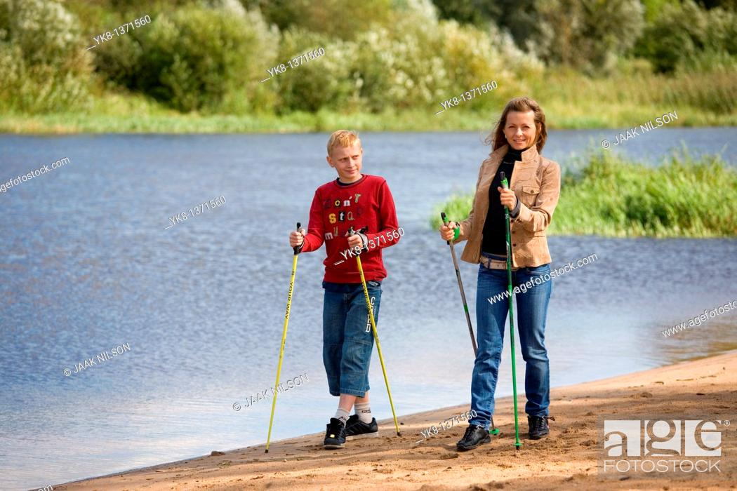 Stock Photo: Young woman and teenage boy doing nordic walking by river water.