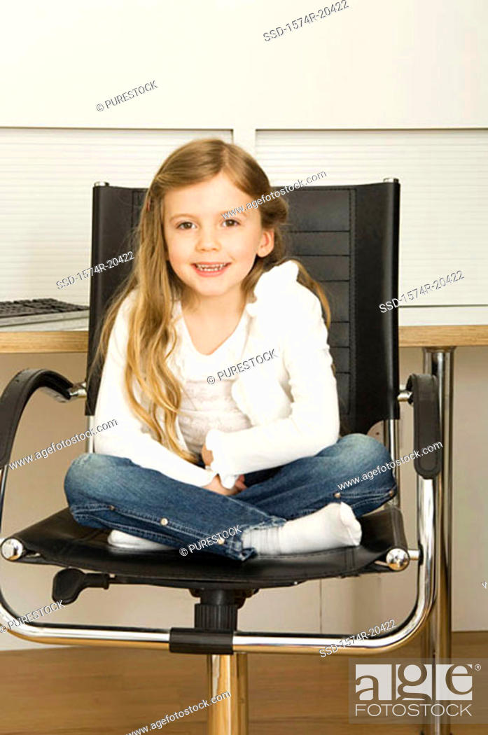Stock Photo: Portrait of a girl sitting in a chair and smiling.