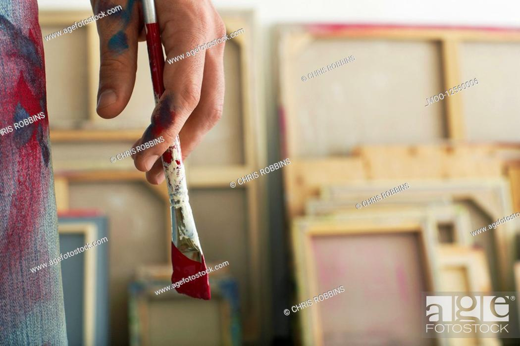 Stock Photo: Artist holding paint brush standing in studio close up on hand.