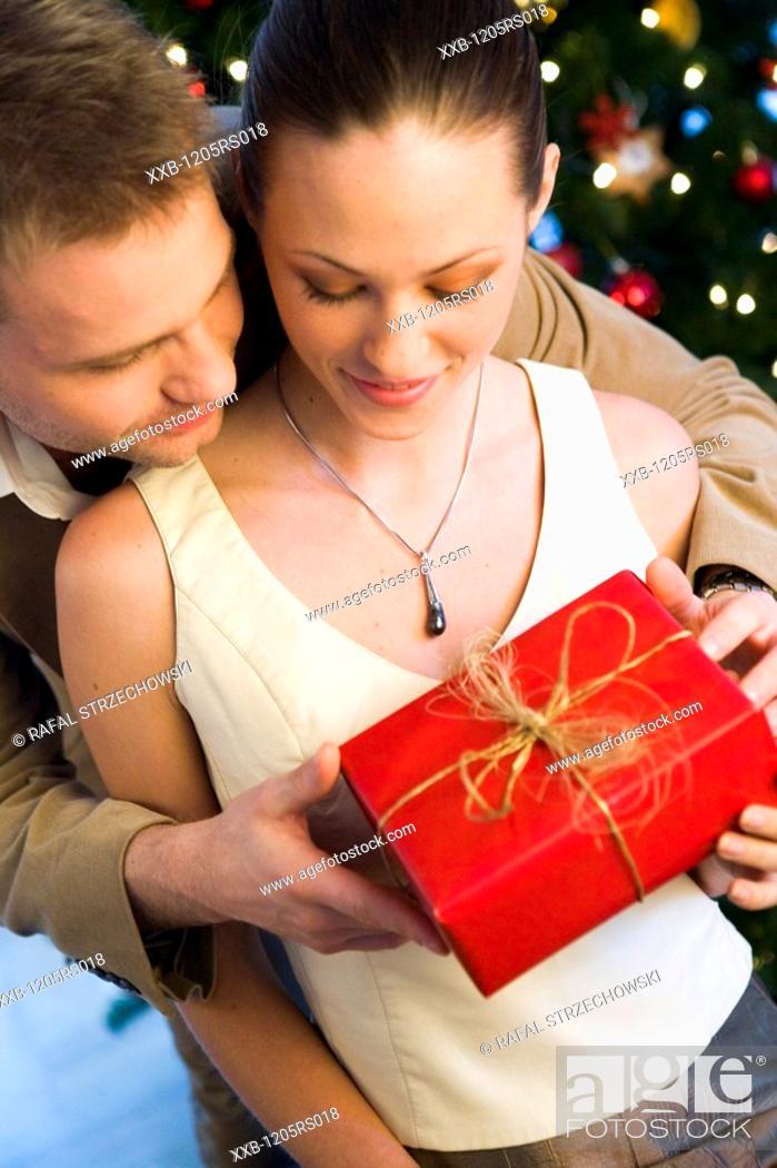 Stock Photo: couple giving themself christmas presents.