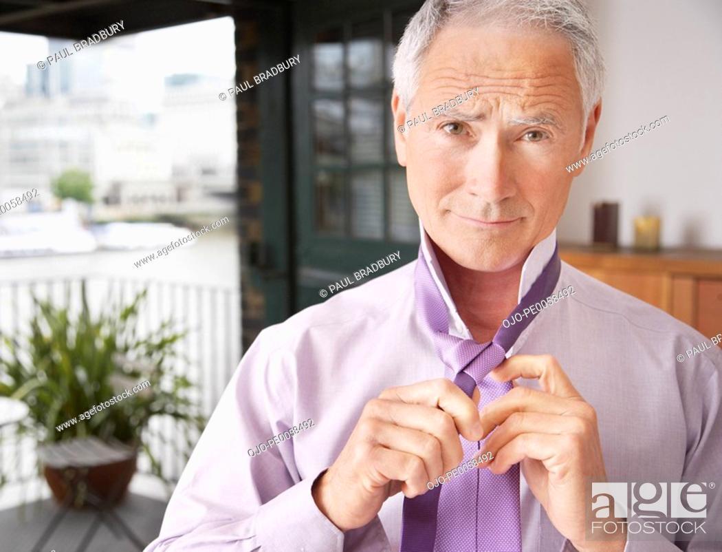 Stock Photo: Man doing up tie in bedroom.