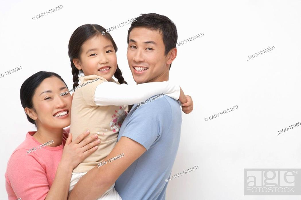 Stock Photo: Family portrait of father holding daughter mother hugging on other side side view.