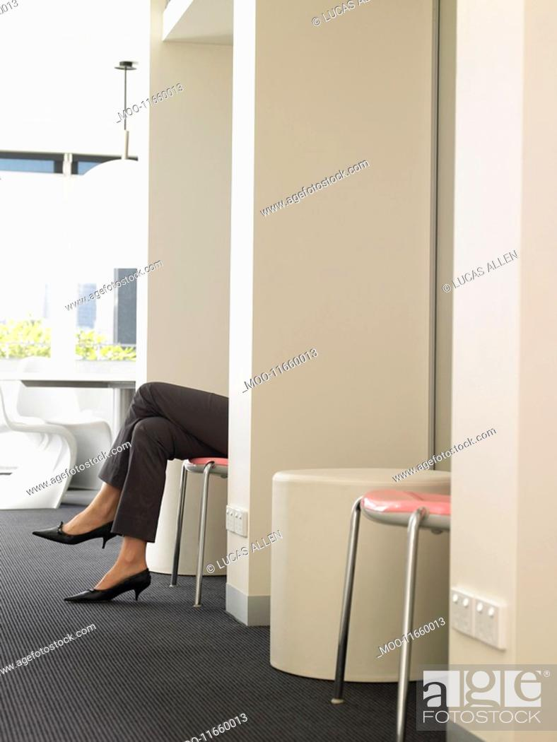 Stock Photo: Businesswoman's legs sticking out of cubicle.