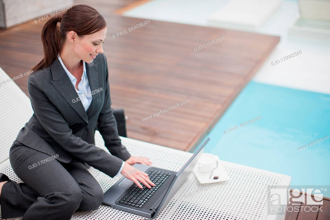 Stock Photo: Businesswoman using laptop on lounge chair outdoors.