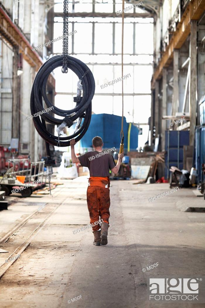 Stock Photo: Rear view of worker pulling piping on winch in shipyard workshop.