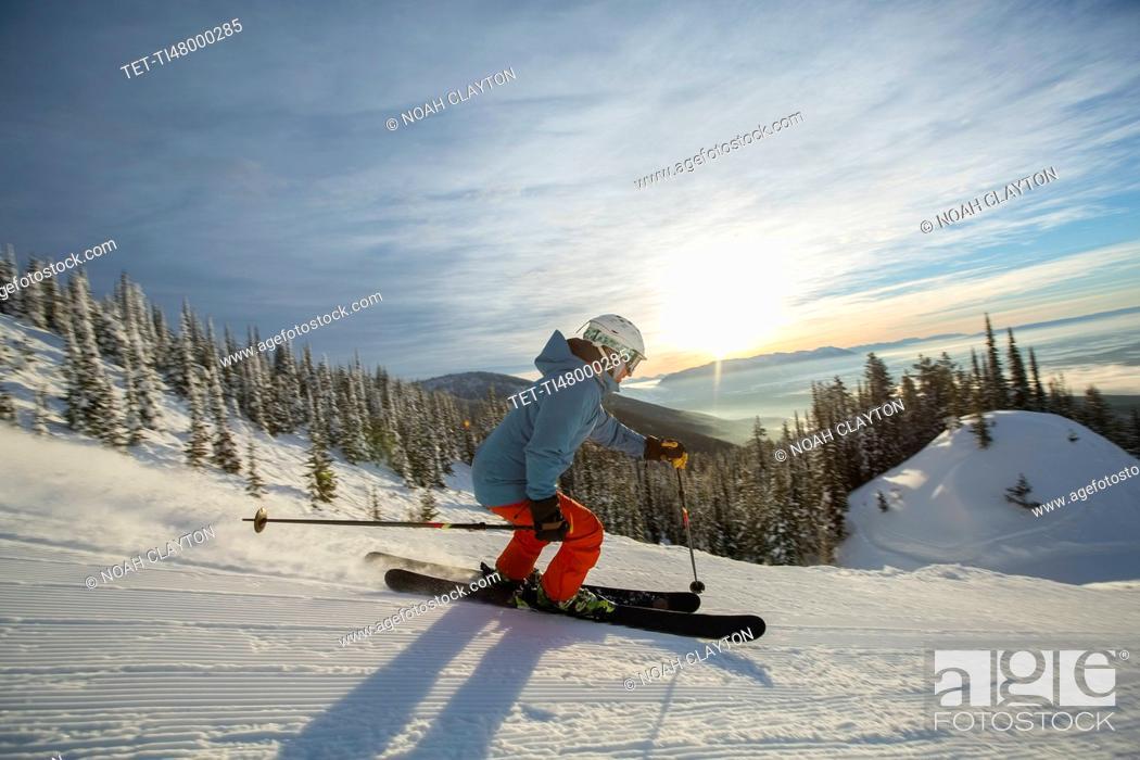 Stock Photo: Mature man on ski slope at sunset.