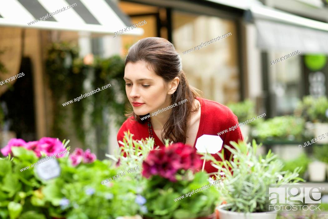 Stock Photo: Woman smelling flowers in a flower shop.