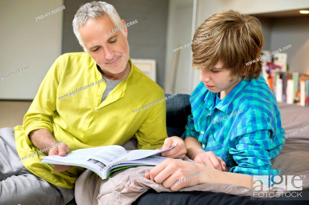Stock Photo: Teenage boy studying with his father at home.
