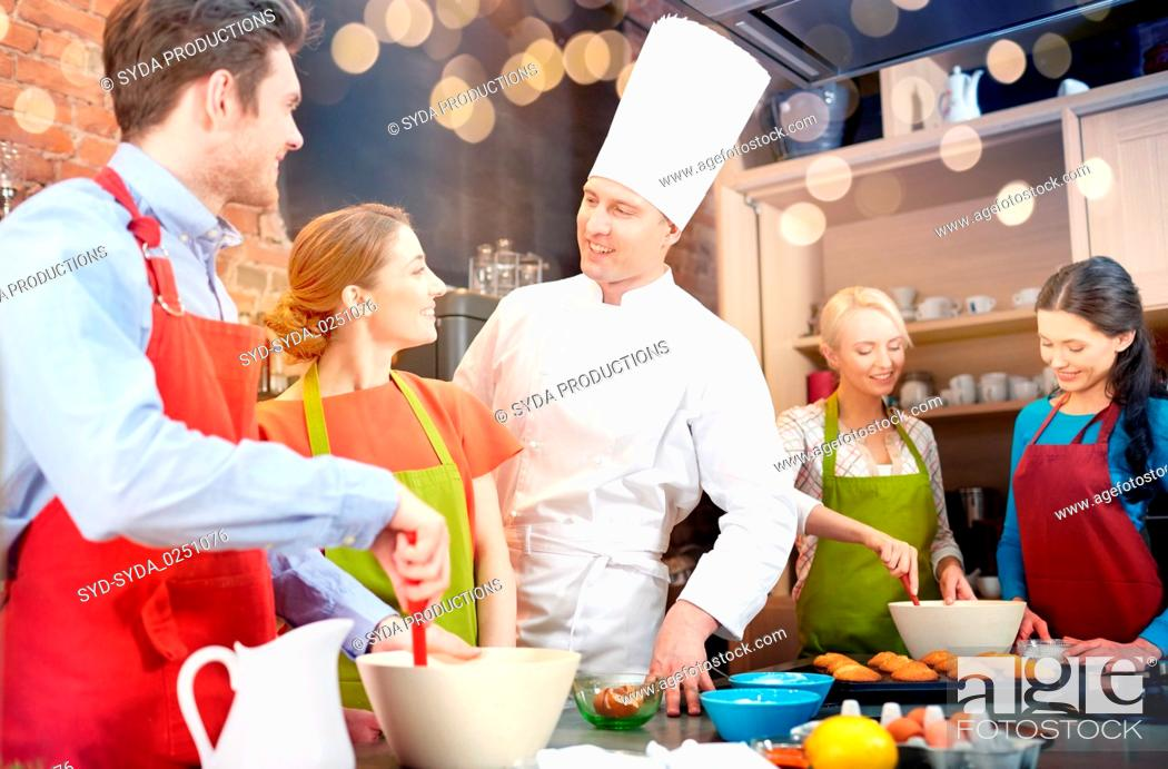 Stock Photo: happy friends and chef cook baking in kitchen.