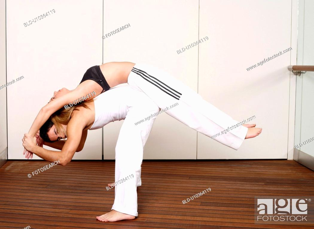 Stock Photo: Partners practicing flexibility in yoga and Capoeira programs.