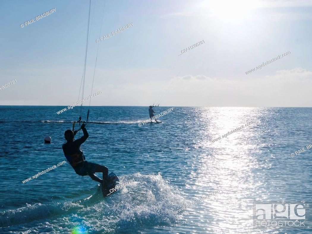 Stock Photo: Parasailing on ocean under sunny blue sky.