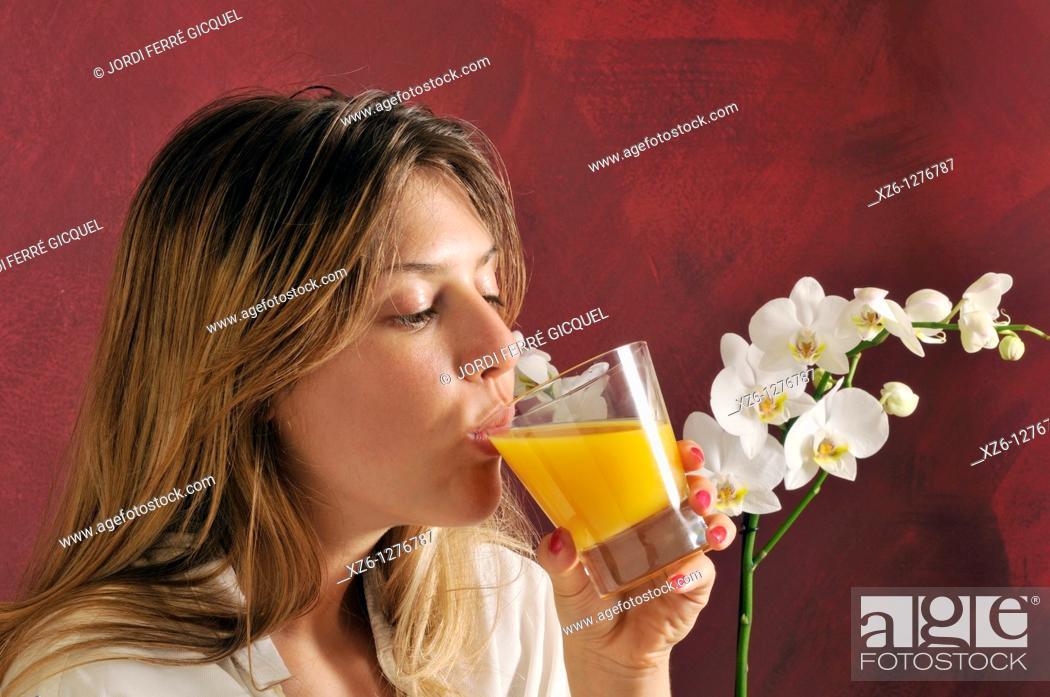 Imagen: Young woman drinking orange juice.