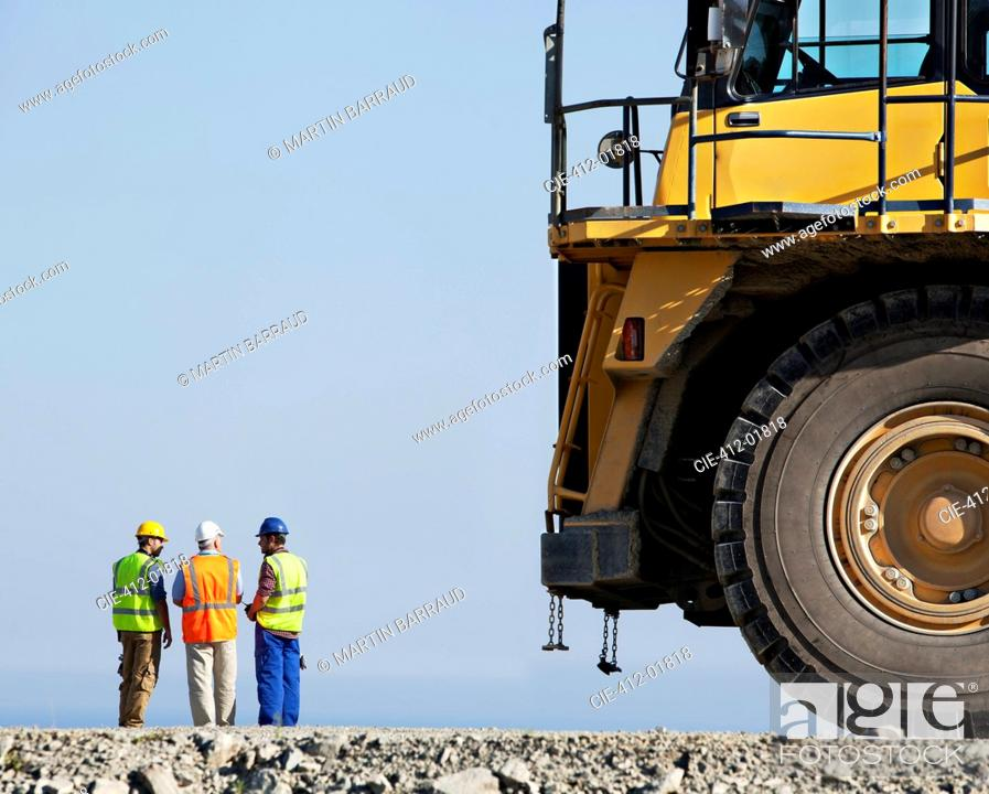 Stock Photo: Workers talking with machinery in quarry.