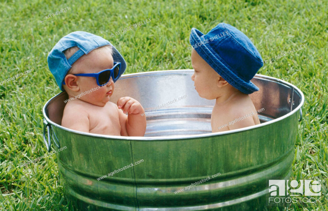 Stock Photo: babies in a outdoor tub.