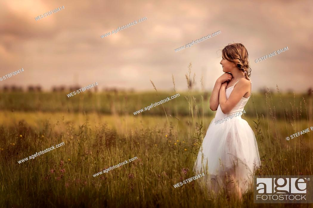 Stock Photo: Girl wearing tutu standing on a meadow.