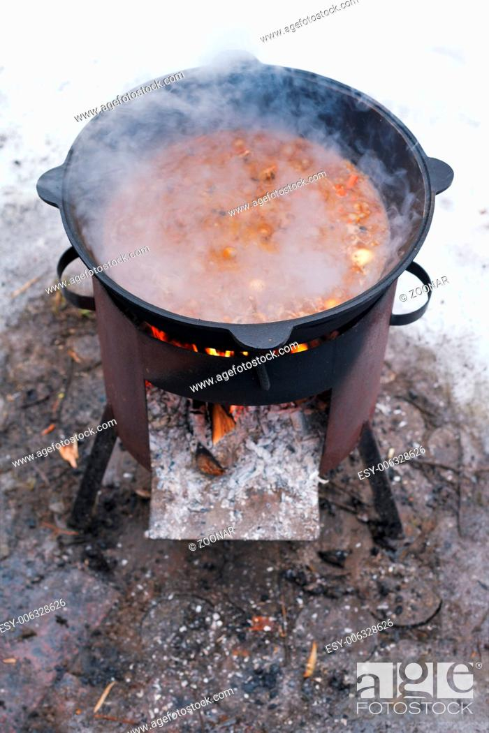 Stock Photo: food stewed in cauldron on mobile brazier.