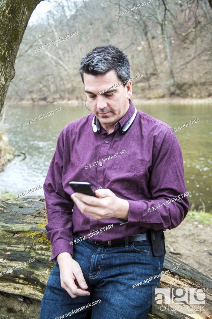 Imagen: Caucasian handsome dark hair man wearing a purple shirt and his bluetooth. He is in against a wood log in nature and he is focused on his phone.