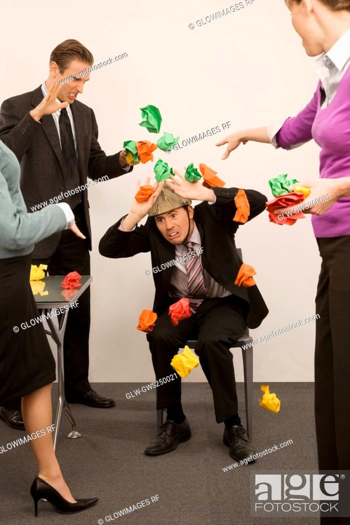 Stock Photo: Businessman protecting himself from colleagues throwing paper balls.