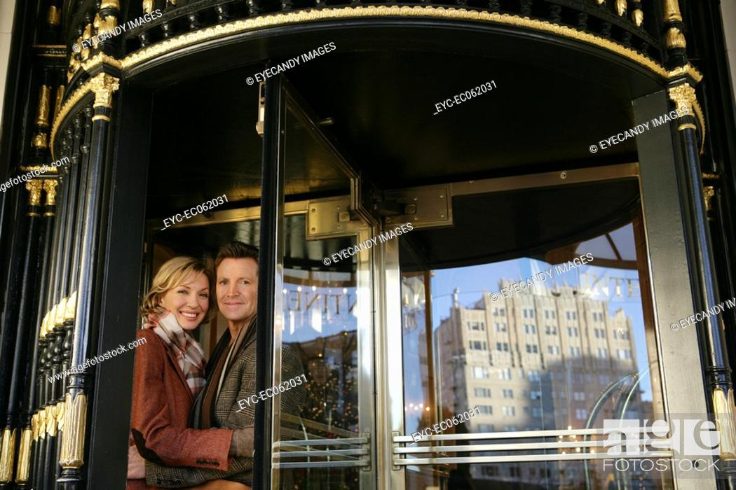 Stock Photo: Mature couple in between revolving doors.
