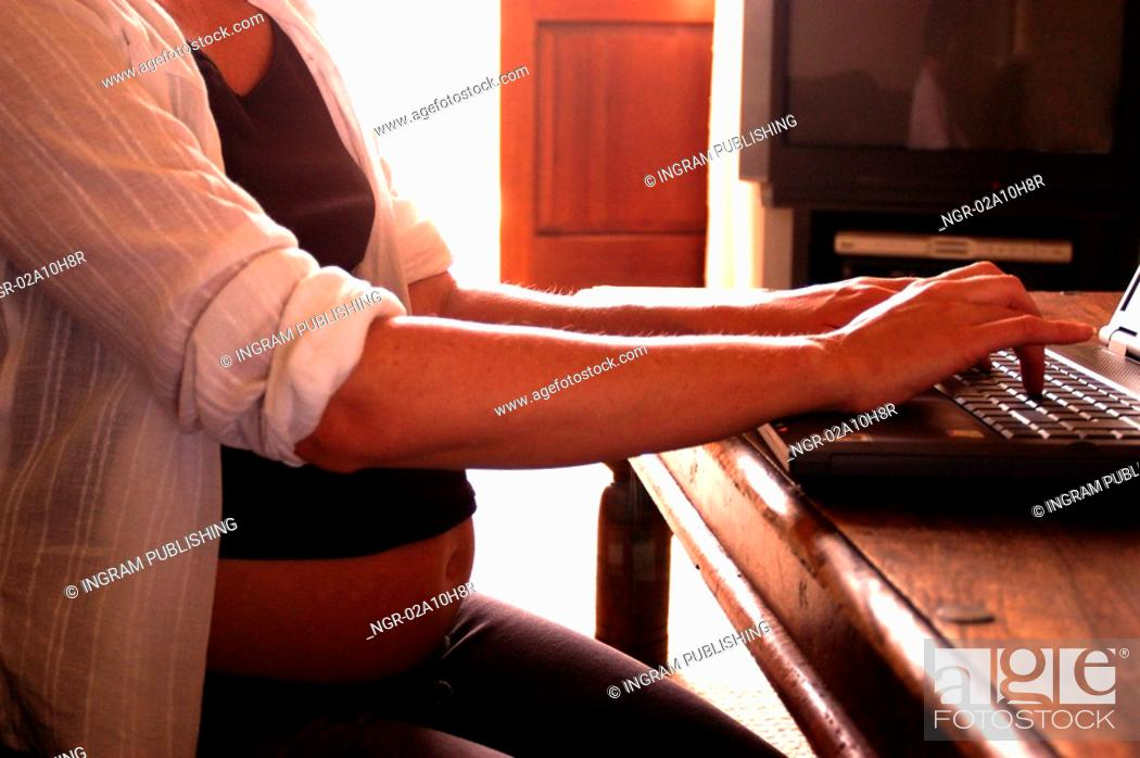 Stock Photo: pregnant woman working on laptop.