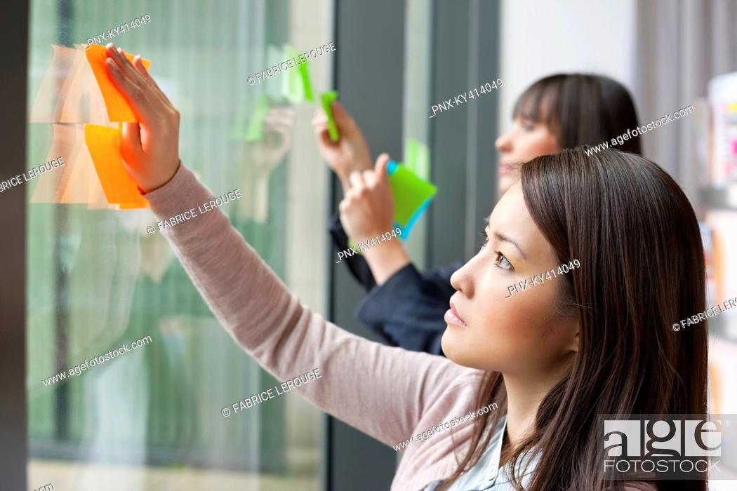 Stock Photo: Businesswomen sticking memo notes on glass in an office.