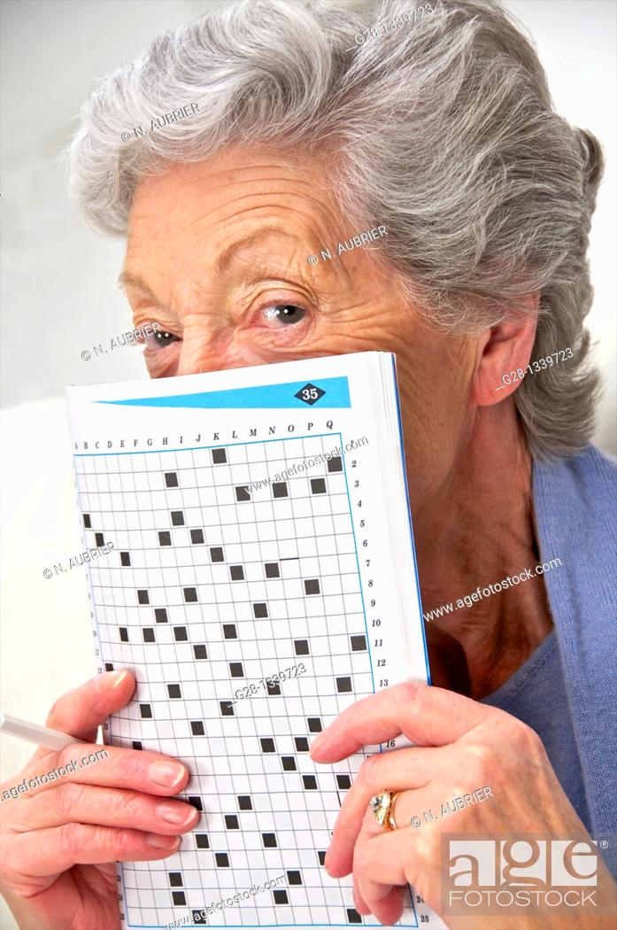 Stock Photo: senior woman in a mauve cardigan, holding a crosswords magazine in front of her at home.