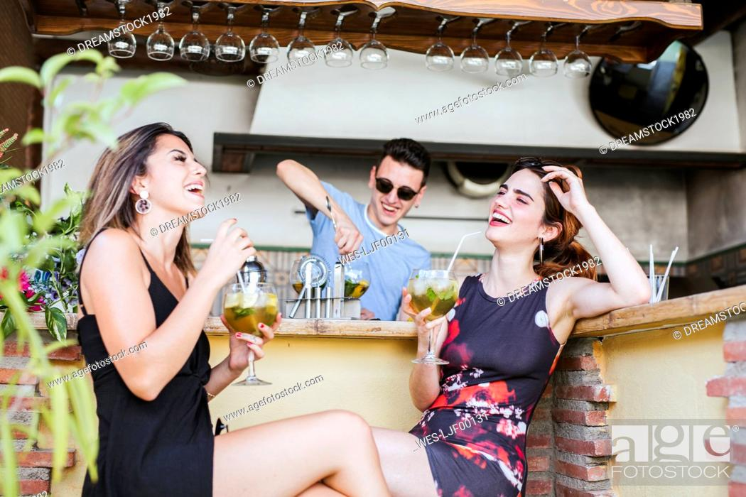 Stock Photo: Two happy women having a drink at a bar.