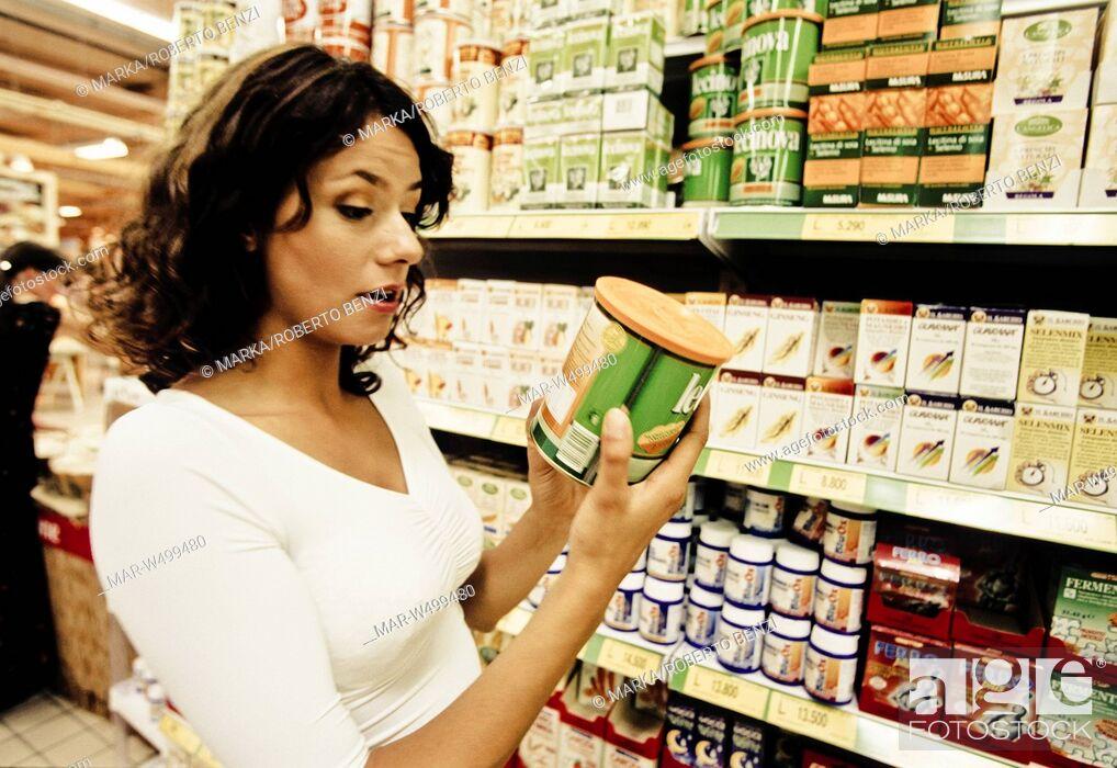 Stock Photo: una donna al supermercato controlla l'etichetta di un prodotto.