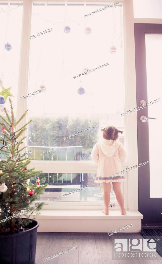 Stock Photo: Curious girl on window ledge below Christmas ornaments.