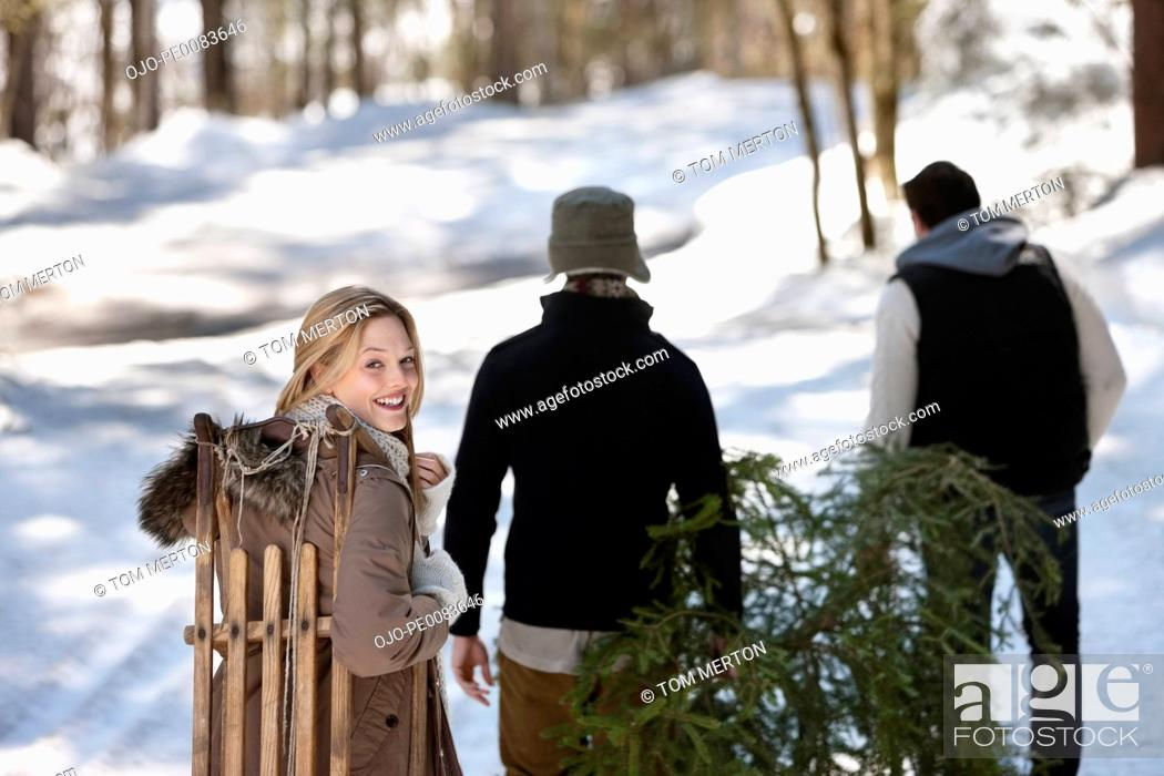 Stock Photo: Friends with fresh cut Christmas tree and sled in snowy woods.