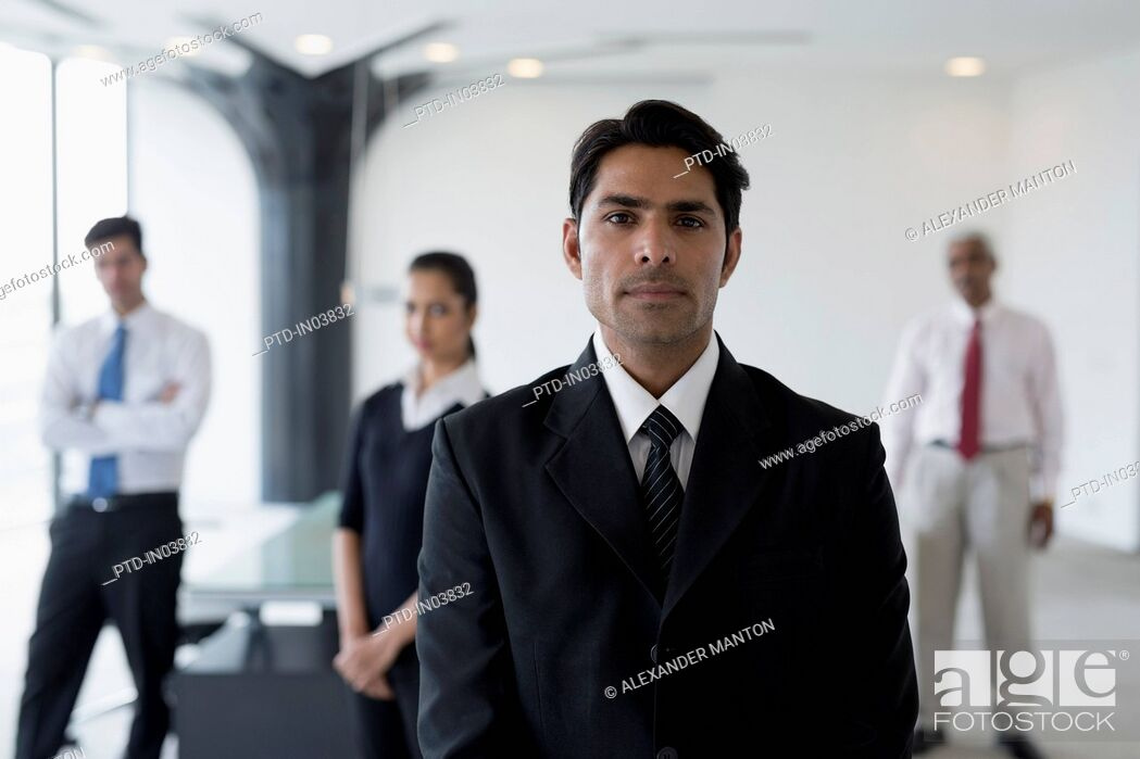 Stock Photo: India, Business man in suit standing in front of colleagues.