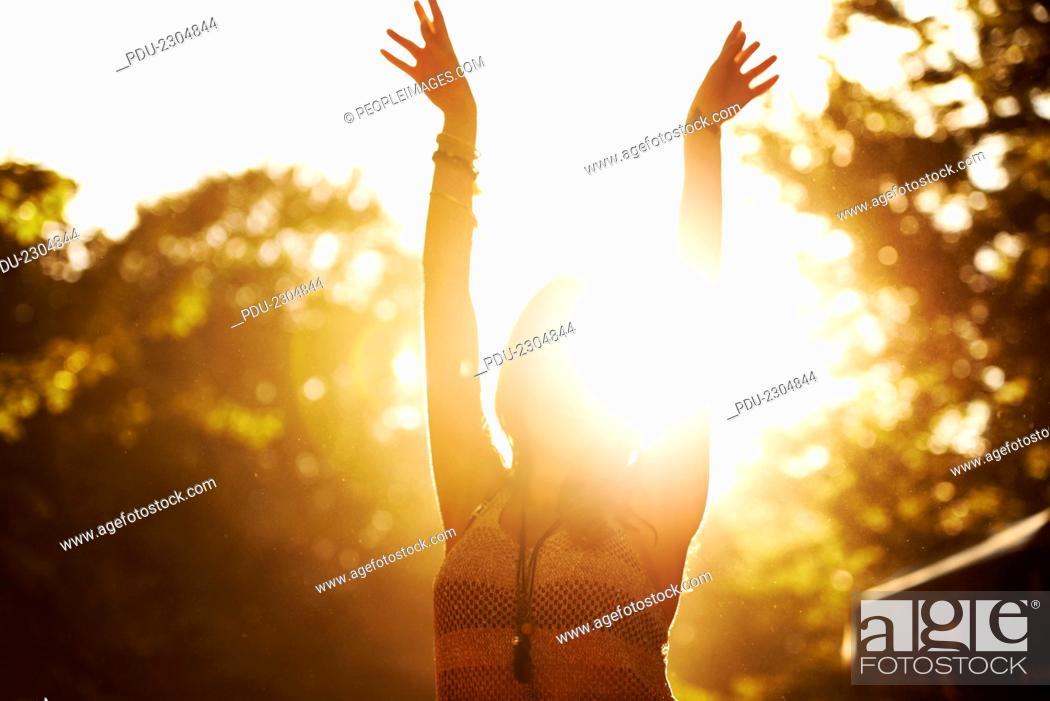 Stock Photo: Backlight shot of a young woman enjoying herself at an outdoor festival.