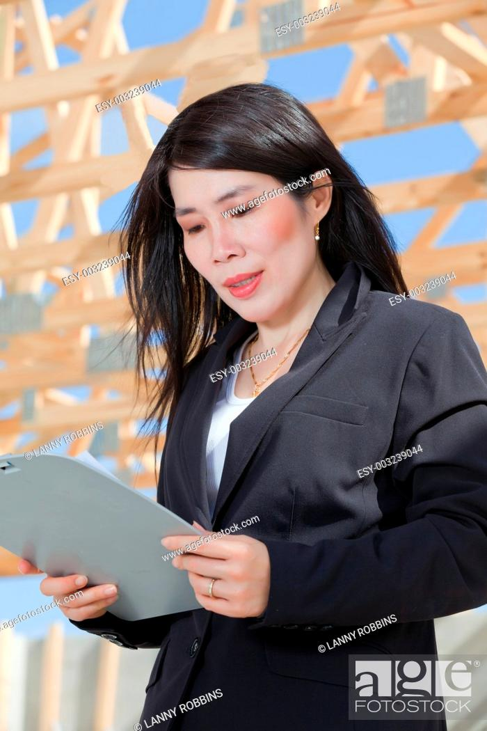 Stock Photo: Asian woman contractor with a set clipboard.