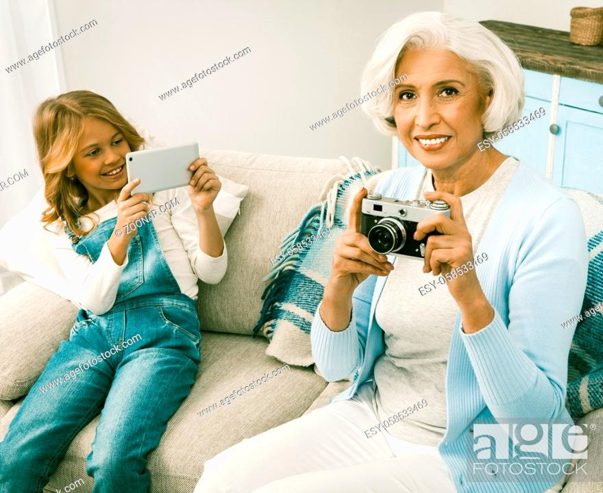 Photo de stock: Granddaughter Taking Photos Or Videos On Her Seasonal Gift For White Haired Italian Grandmother Upgrading Her With New Smartphone.