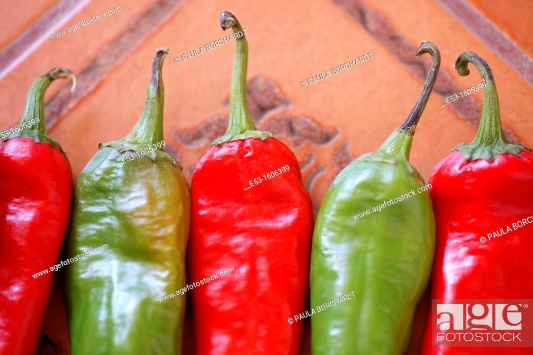 Stock Photo: Red and green organic Anaheim chiles on Spanish tile, Tucson, Arizona, USA.