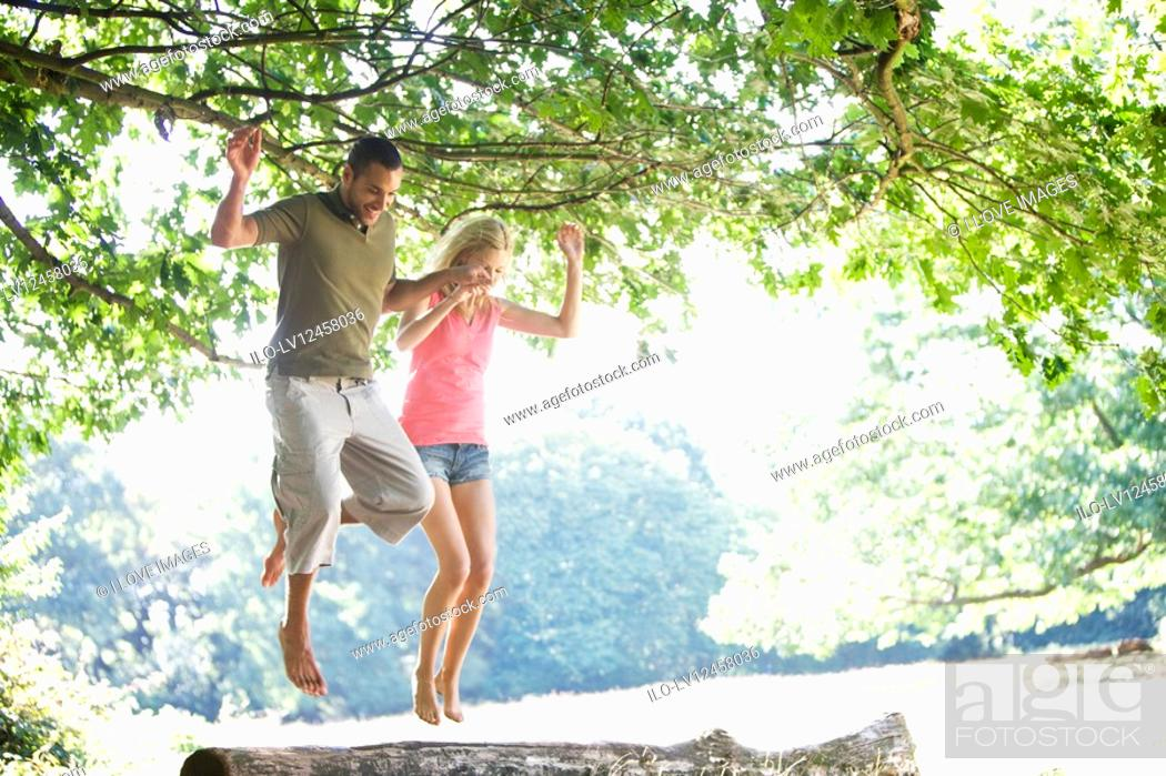 Stock Photo: A young couple jumping from a log.