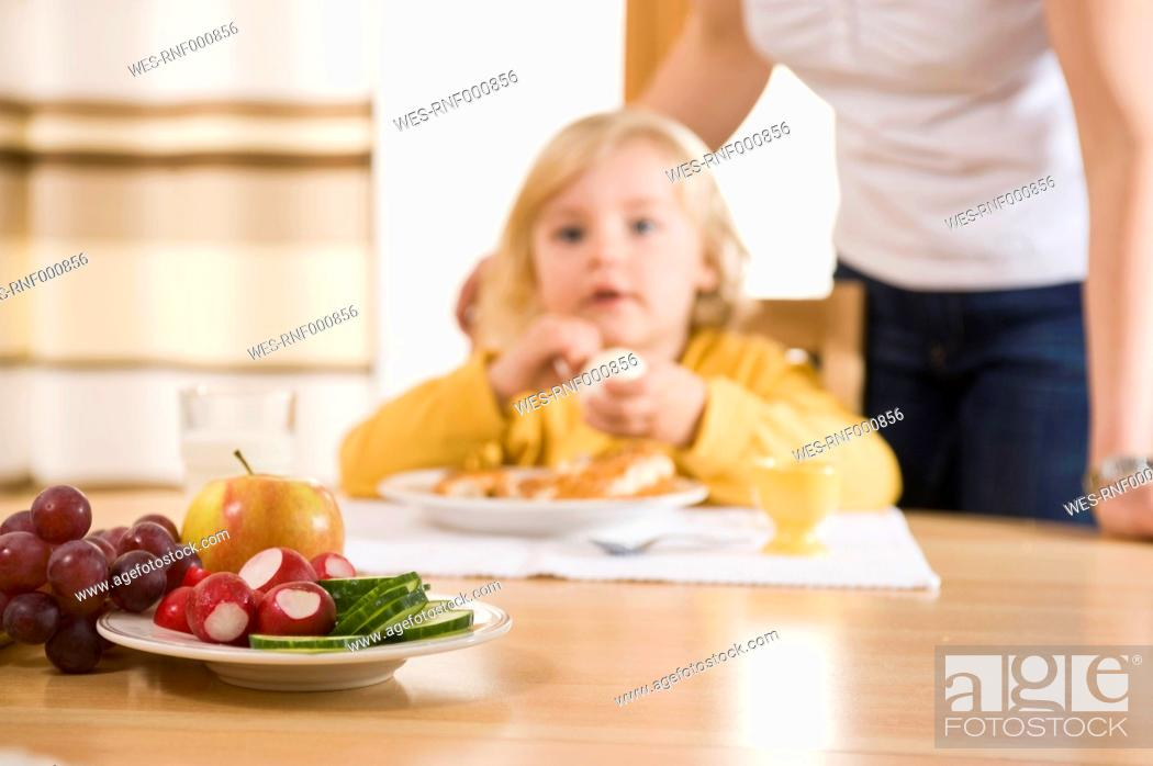 Stock Photo: Fresh fruits on table, girl having breakfast in background.