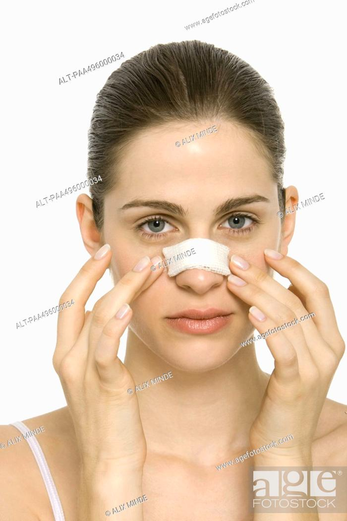 Stock Photo: Young woman with bandaged nose, touching face, portrait.