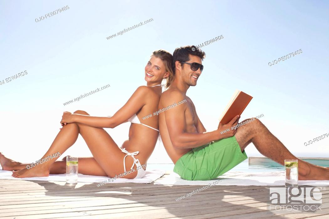 Stock Photo: Couple in bathing suits sitting back to back.