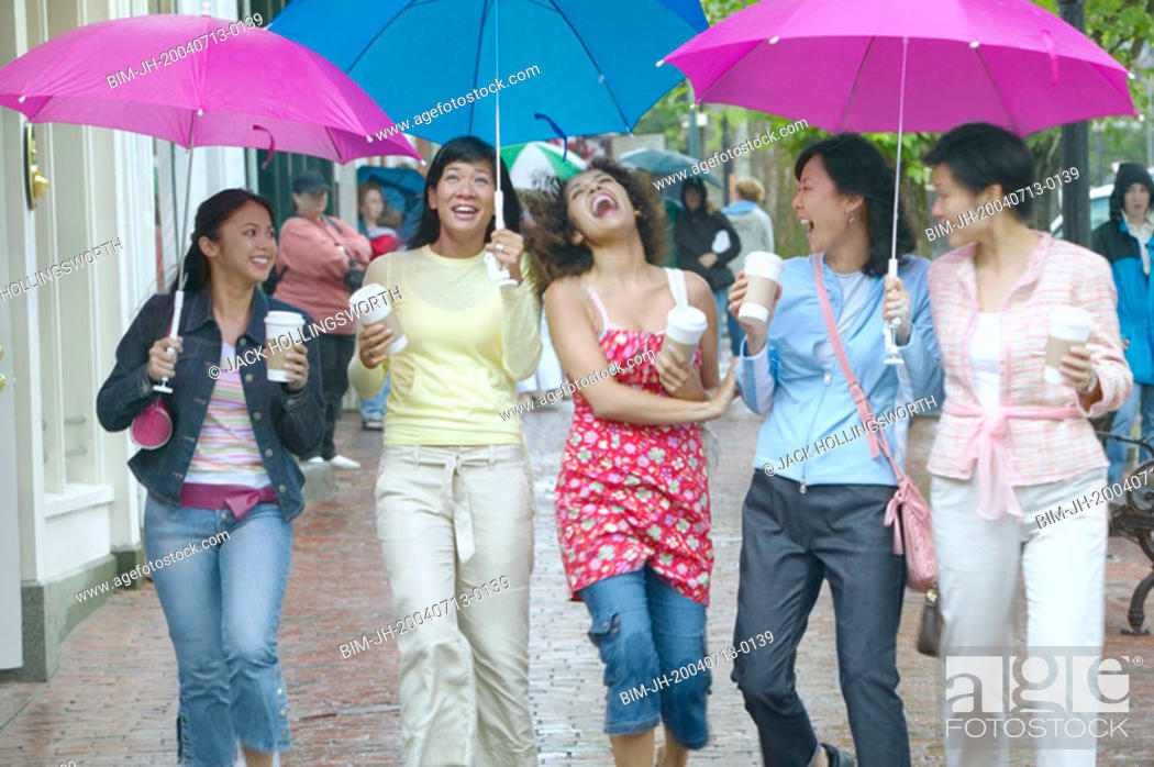 Stock Photo: Group of women walking and laughing with umbrellas.