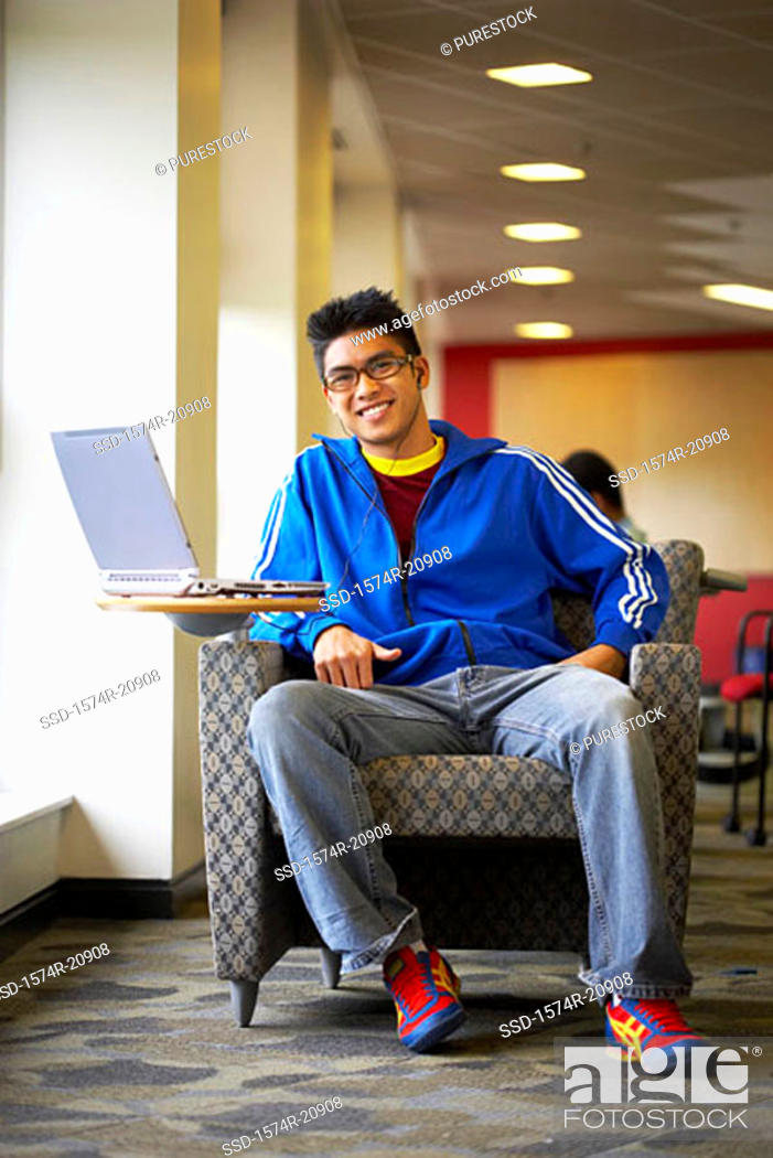 Stock Photo: Portrait of a college student sitting in an armchair and smiling.