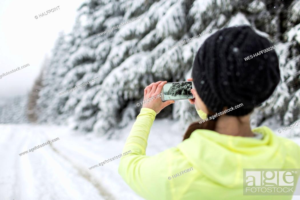 Stock Photo: Woman on snowy road taking picture with smart phone.