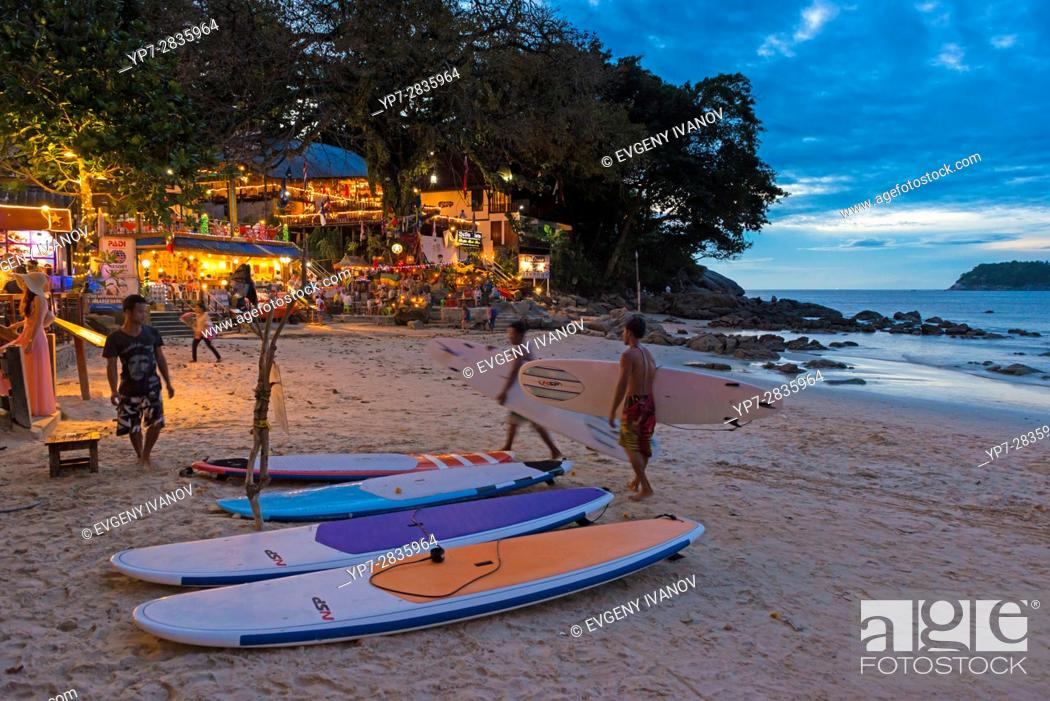 Stock Photo: Surfers walking with surf boards at night to the rent shop on Kata beach, Phuket, Thailand.