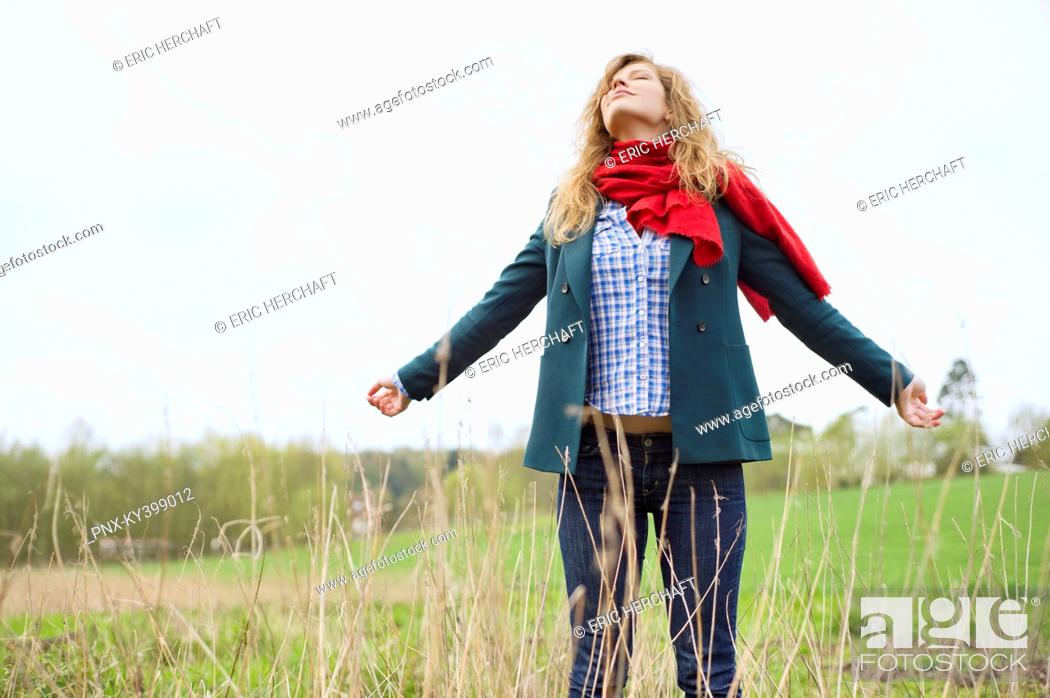 Stock Photo: Beautiful woman daydreaming in a field.