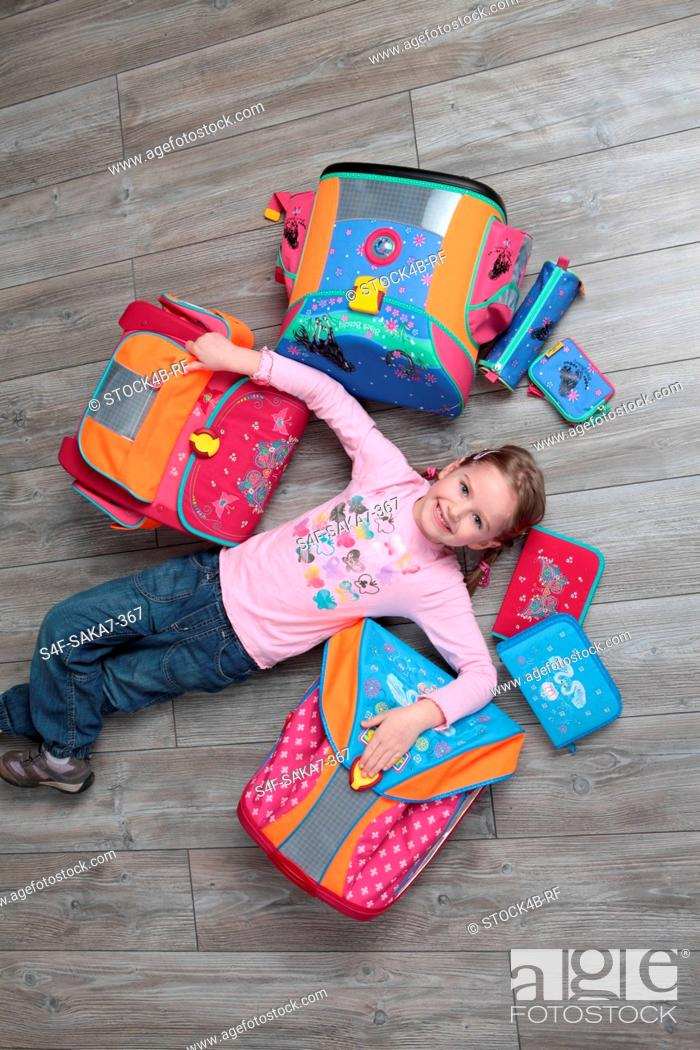 Stock Photo: Smiling girl surrounded by schoolbags.