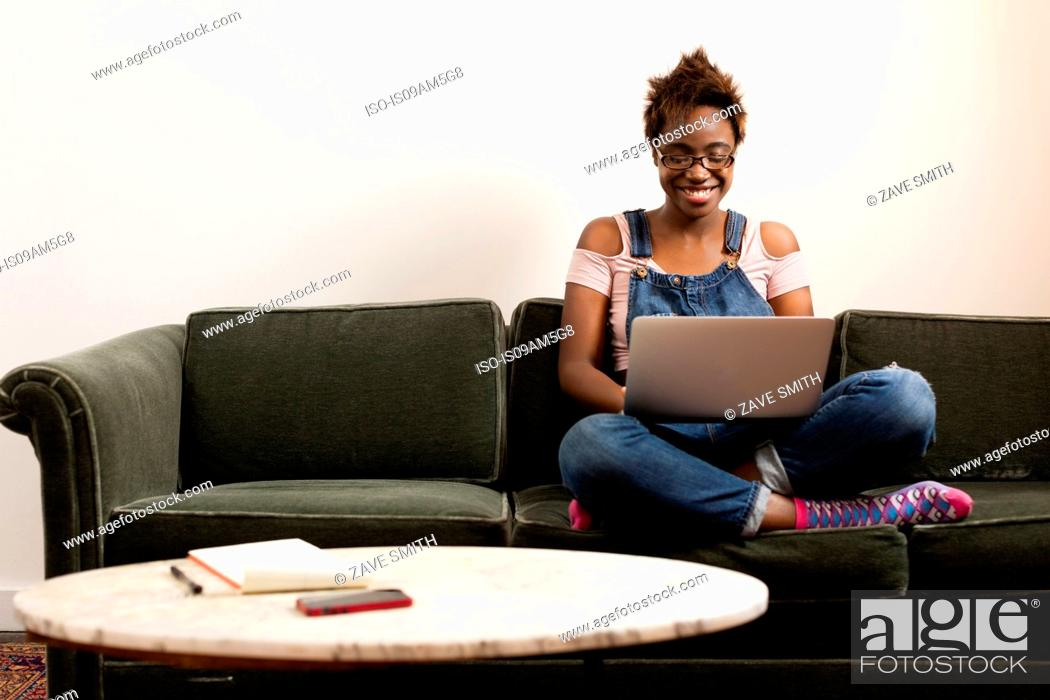 Stock Photo: Woman working at laptop on sofa.