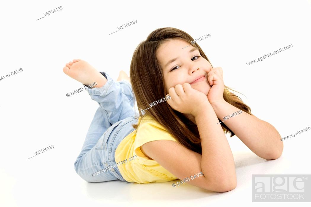 Stock Photo: Five year old female child laying on white background smiling wearing casual clothes.