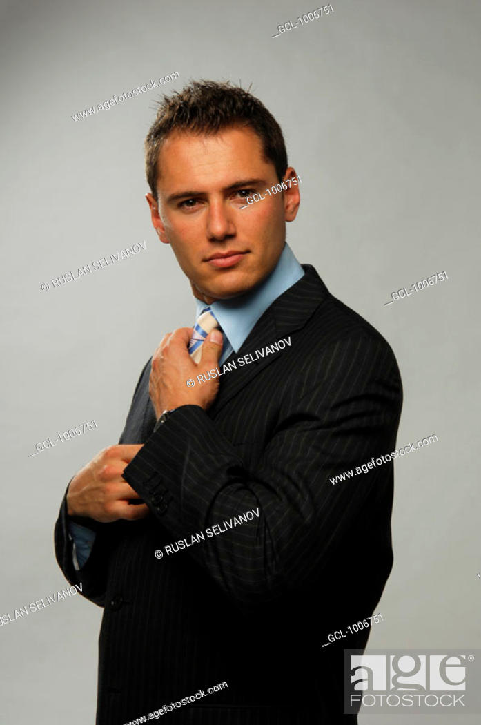Stock Photo: Portrait of a businessman adjusting his tie.